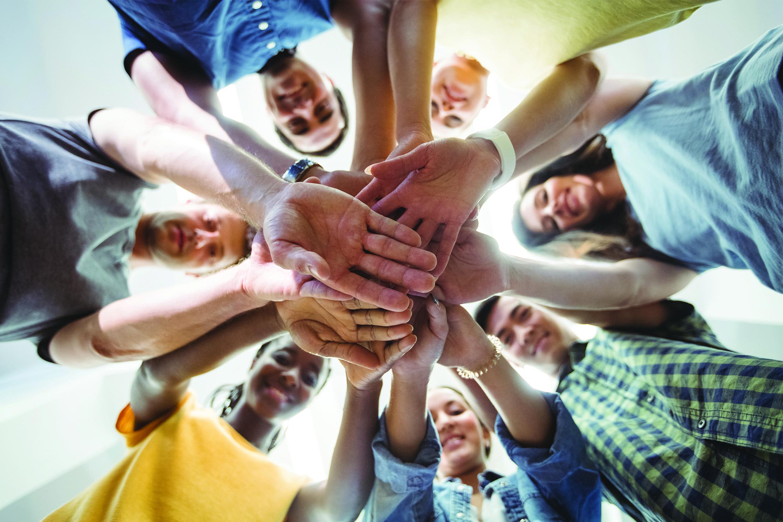 Sept individus de diverses origines s'unissent par les mains